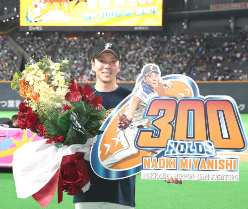 日本ハム対ロッテ 通算300ホールドを達成しボードを掲げる宮西(撮影・黒川智章)