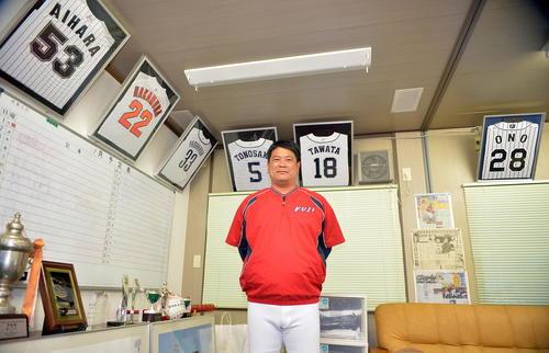 プロ野球に進んだ教え子たちのユニホームに囲まれる富士大・豊田監督(撮影・鎌田直秀)