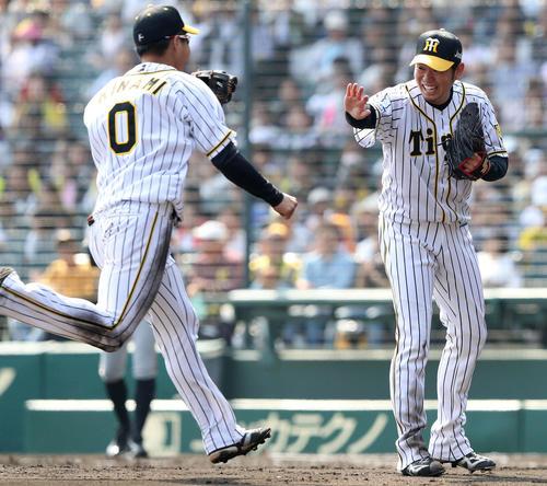 阪神対巨人 2回表巨人2死一塁、西(右)は山本の打球を好捕した遊撃木浪を笑顔で迎える(撮影・松本俊)