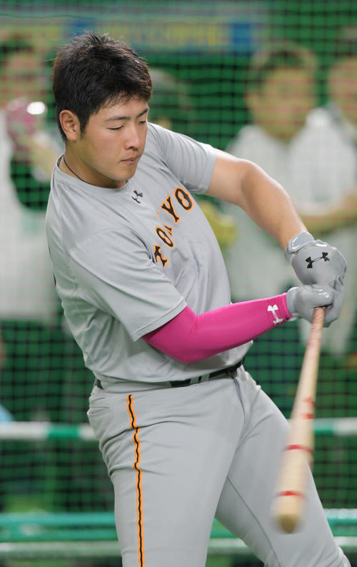 試合前、ピンク色のアームカバーをつけて打撃練習をする巨人の岡本(撮影・加藤諒)