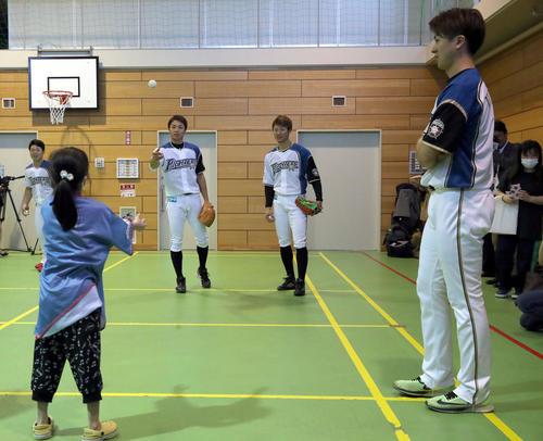 北海道大学病院内にあるひまわり分校に通う児童や生徒たちとキャッチボールをする日本ハム中島とそれを見つめる西川と上沢(撮影・佐藤翔太)