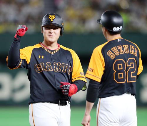 1回裏1死二塁、中前適時打を放ちガッツポーズする岡本(左)(撮影・垰建太)