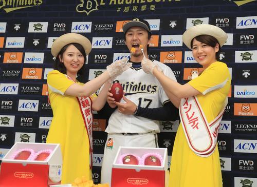 宮崎サンシャインレディの須藤里紗さん(左)と今井千尋さんからマンゴーを食べさせてもらう増井浩俊