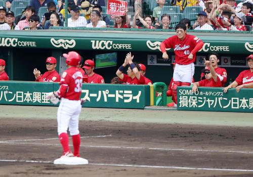 4回表広島2死一塁、菊池の右越え適時三塁打に笑顔を見せる緒方監督(左)とベンチのナインたち(撮影・加藤哉)