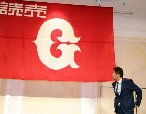 引退会見を終えて記念撮影をする直前、巨人の球団旗を見つめる上原(撮影・浅見桂子)