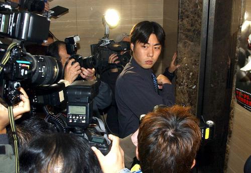 加藤弁護士に遅れて契約更改に向かった上原は、報道陣に囲まれ厳しい表情を見せる(2003年11月27日撮影)