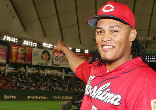 巨人対広島 ヒーローインタビュー後、8回表のソロ本塁打で直撃させ、100万円をゲットした看板(左側)を指さすバティスタ(撮影・狩俣裕三)