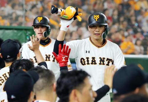 巨人対広島 8回裏巨人1死二塁、2点本塁打を放ちナインの出迎えを受ける坂本勇人(右)と陽(撮影・垰建太)