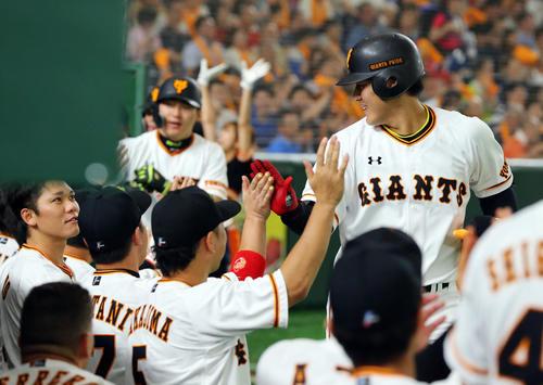巨人対広島 1回裏巨人1死一、二塁、左越え3点本塁打を放ちベンチでナインに迎えられる中坂本勇(左)にらまれる岡本(撮影・垰建太)