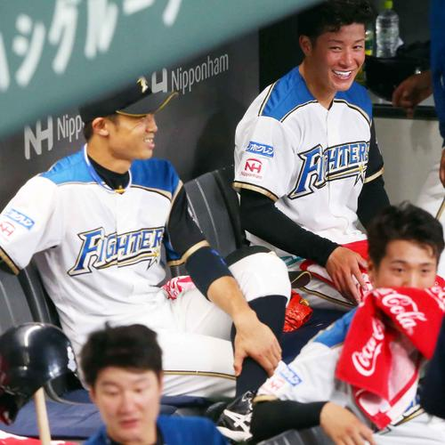5回を投げ終えた吉田輝(右奥)はベンチに戻りナインのやりとりに笑顔を見せる(撮影・垰建太)