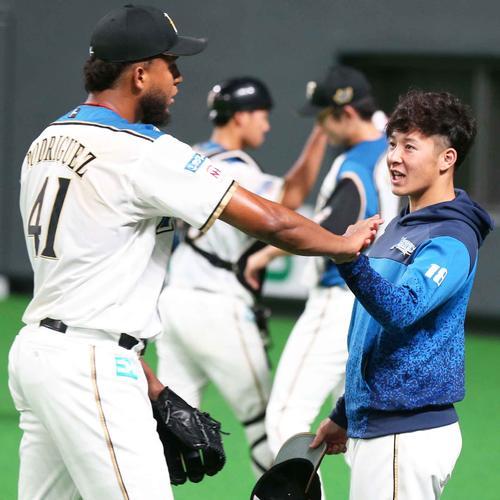 8回表、打者を3人で抑えたロドリゲス(左)を笑顔で出迎える吉田輝(撮影・黒川智章)