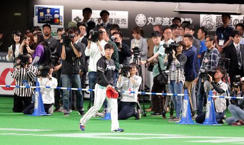 日本ハム対広島 大勢の報道陣の前を通りグラウンドに入る日本ハム吉田輝(撮影・佐藤翔太)