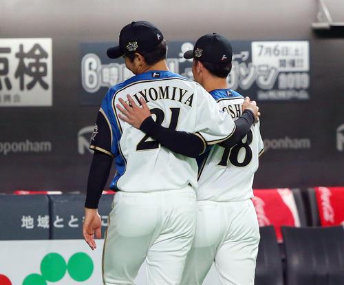 日本ハム対巨人 試合前、ファンとのハイタッチを終えた日本ハム吉田輝星(右)と清宮幸太郎は肩を組んで引き揚げる(撮影・垰建太)