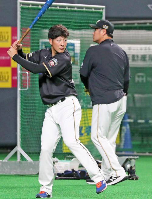 試合前、真剣な表情で素振りする日本ハム吉田(左)。右は木田コーチ(撮影・垰建太)