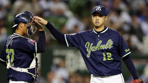試合後、古賀(左)とタッチを交わす石山(撮影・狩俣裕三)