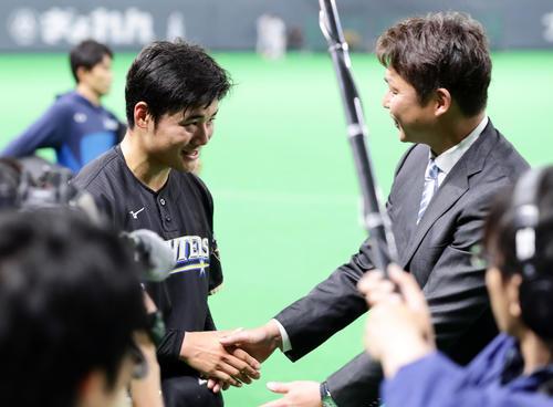 日本ハム対巨人 試合前、新井貴浩氏(右)からインタビューを受け握手する清宮(撮影・浅見桂子)