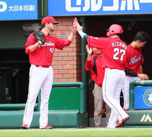 6回表広島2死三塁、バティスタの左越え適時二塁打で生還した会沢(右)はジョンソンとタッチを交わす(撮影・足立雅史)
