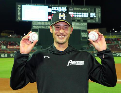 18年6月、広島戦で日本ハム上原は左手に本塁打球、右手に勝利球の2つの記念球を手に笑顔を見せる