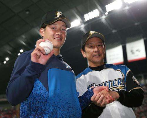 12日、プロ初登板初勝利を挙げウイニングボールを手に笑顔の日本ハム吉田輝(左)。右は栗山監督
