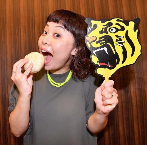 なるみは551蓬莱の豚まんを手に「ある時~」と笑顔で阪神タイガースを応援する(撮影・上田博志)