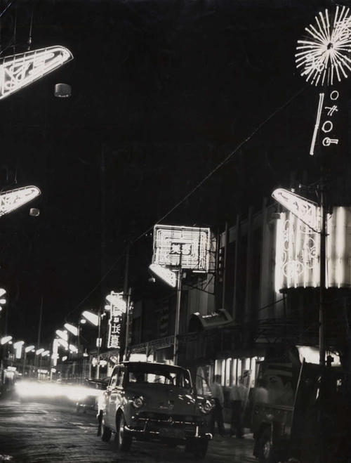 尼崎中央商店街の夜景。右上に丸い、中央に四角い「春美」のネオンが見える(55年撮影、兵庫県尼崎市立地域研究史料館所蔵)