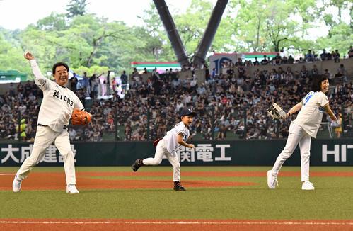 西武対ロッテ 始球式で投球する西武OBの東尾氏(左)。中央は孫の理汰郎くん。右は東尾理子さん(撮影・滝沢徹郎)