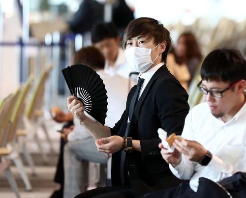 新千歳空港の待合室で扇子であおぐ日本ハム金子(撮影・黒川智章)