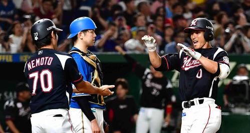 日本ハム対ロッテ 2回表ロッテ2死一塁、荻野(右)は左越えに2打席連続の2点本塁打を放ち根元一塁コーチの祝福を受ける(撮影・小沢裕)