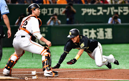 巨人対阪神 1回表阪神1死満塁、ソラーテの中犠飛で三塁走者の木浪はヘッドスライディングで生還する。捕手小林(撮影・小沢裕)