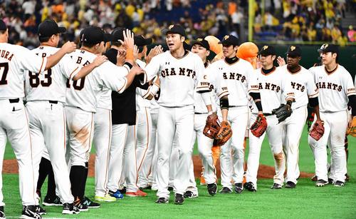 巨人対阪神 自身キャリアハイとなる本塁打が決勝打となった巨人坂本勇(中央)は歓喜のナインとハイタッチ(撮影・小沢裕)