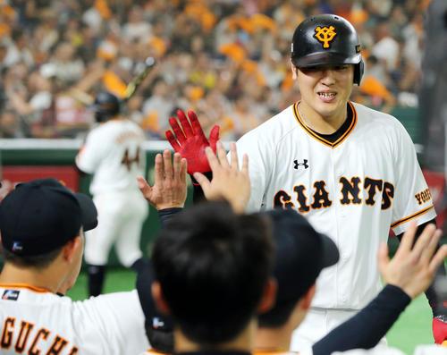 巨人対阪神 5回裏巨人2死、左越えソロ本塁打を放ちナインの出迎えを受ける岡本(撮影・垰建太)