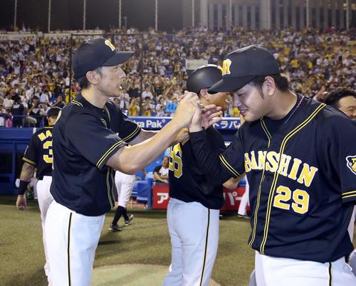 3勝目を挙げ、矢野監督(左)とタッチを交わす高橋遥(撮影・前田充)