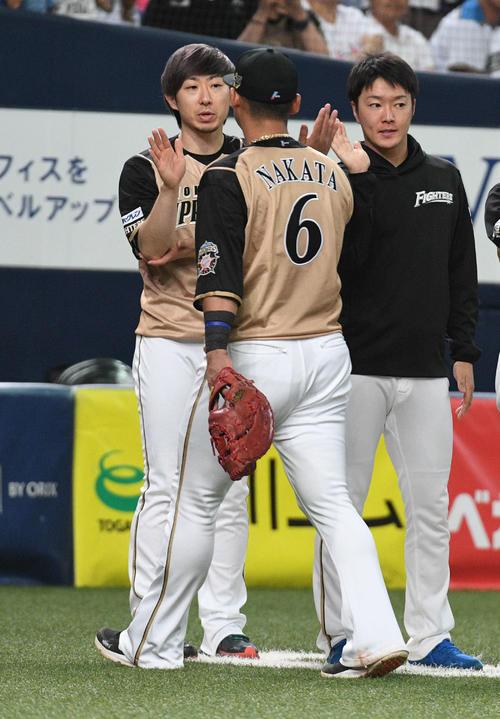 オリックス対日本ハム 5勝目を挙げた金子(左)は復帰戦で2点適時二塁打を放った中田(中央)らとハイタッチ(撮影・渦原淳)