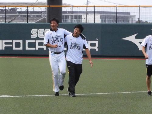 ソフトバンク江川(左)は外野守備練習中に左足ふくらはぎを痛め引き揚げる