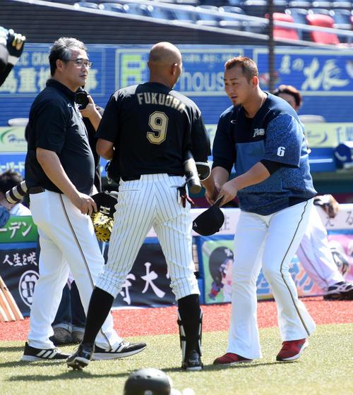 引退試合を前に、日本ハム中田(右)と握手するロッテ福浦、左は日本ハム木田投手コーチ(撮影・柴田隆二)