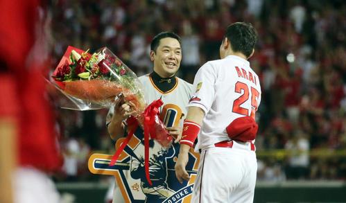 阿部は右前打で2000安打とし、花束を持参した広島新井に笑顔を見せる(2017年8月13日)