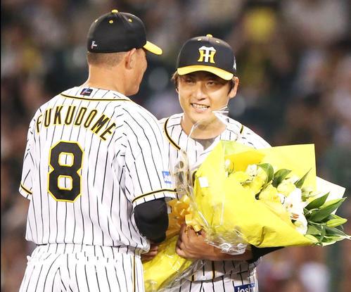 7回表中日無死、最終登板を終えた高橋聡(右)は福留から花束を贈られ笑顔を見せる(撮影・上山淳一)
