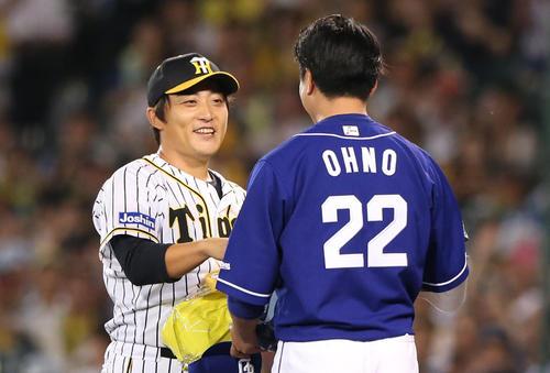 7回表中日1死、最終登板を終えた高橋聡(左)は、大野雄からの花束に笑顔を見せる(撮影・上山淳一)