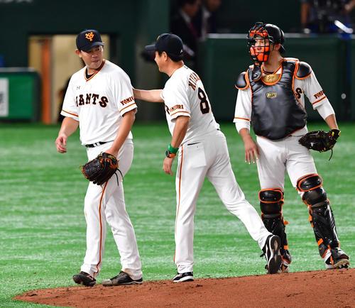 巨人対阪神 8回表阪神1死一塁、降板となり宮本コーチ(中央)からねぎらいを受ける山口(左)(撮影・清水貴仁)