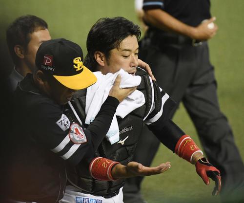 4回裏西武2死一塁、メヒアの打球を追いネット裏のフェンスに激突し、顔をタオルで覆ってベンチに下がる捕手の高谷(撮影・今浪浩三)