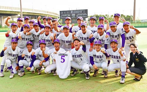 リーグ優勝を決め、福丸和起さんのユニホームとともに記念撮影を行う天理大ナイン(撮影・清水貴仁)