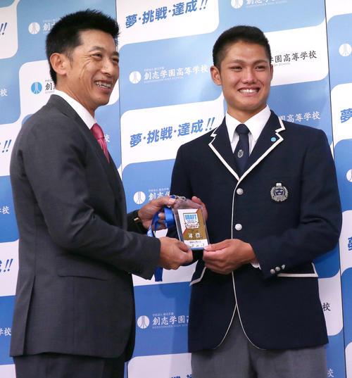 指名あいさつ後、矢野監督(左)自らが書いたサイン入りドラフトIDを受け取り笑顔を見せる創志学園の西(撮影・上山淳一)
