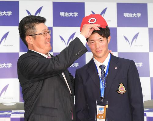 1位指名した明大・森下(右)に帽子をかぶせる広島佐々岡監督(撮影・加藤諒)