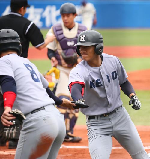 慶大対明大 1回表、中越え2点本塁打を放ちタッチを交わす柳町(右)(撮影・足立雅史)