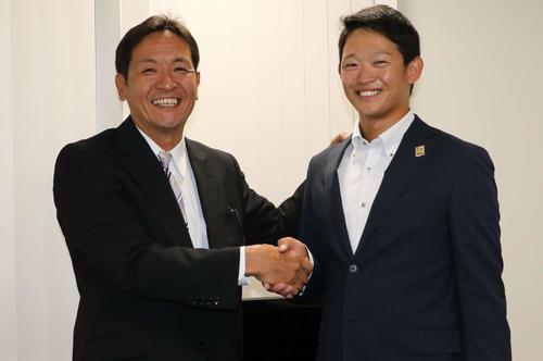 日本ハムからドラフト4位指名を受け、坂本スカウト(左)と握手を交わして笑顔を見せるJX-ENEOS・鈴木(撮影・山崎純一)