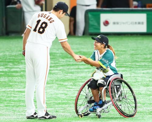 巨人対ソフトバンク 始球式を務めた車いすテニスの上地(右)は巨人菅野と握手を交わす(撮影・足立雅史)
