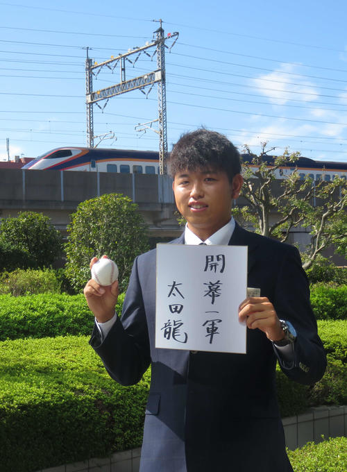 巨人ドラフト2位のJR東日本・太田は通過する新幹線をバックに、「開幕一軍」と目標を書いた色紙とボールを手にポーズをとる(撮影・桑原幹久)