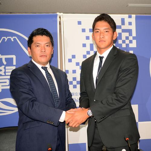 阪神から育成2位指名された静岡大の奥山外野手(右)は高山監督と握手する