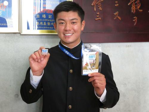 楽天からドラフト3位指名を受けた津留崎は石井GMのサインが入ったドラフトIDを受け取り笑顔(撮影・亀山泰宏)