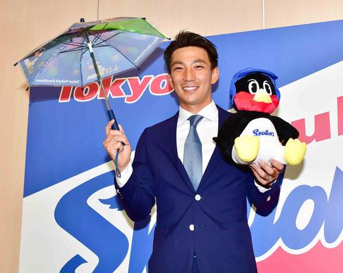 嶋はヤクルトと正式契約しビニール傘とつば九郎のぬいぐるみを手に笑顔を見せる(撮影・小沢裕)